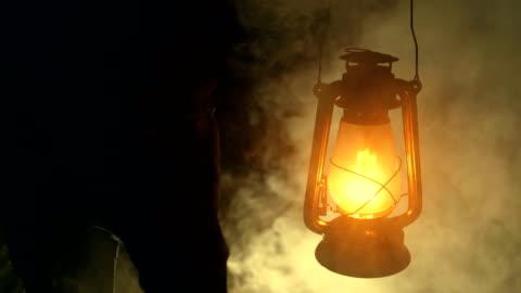 vidéos et rushes de main d'homme tenant une lampe à pétrole dans la nuit - lanterne