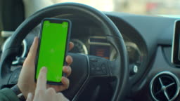 Man hand holding a smartphone with green blank screen in the electric car for direction, massage, location, business. Man sits in modern electric car and works on smartphone - green screen - closeup. Chroma key.