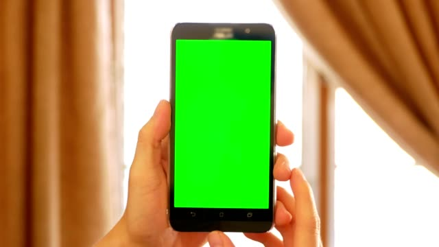 man hand holding mobile smart phone with green screen for chroma key - domestic indoor scene - portability stock videos & royalty-free footage