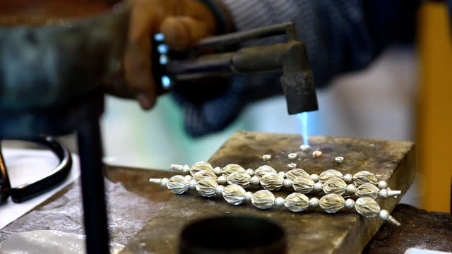 man hand making silver necklace with gas burning to bond
