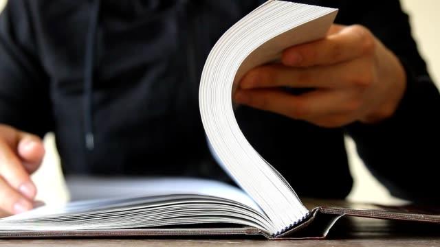 vídeos de stock, filmes e b-roll de mão do homem que abre e que lanç o livro na tabela - livro