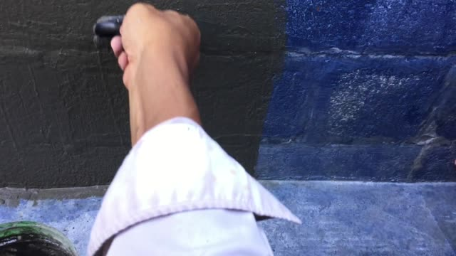 Man hand painting concrete wall