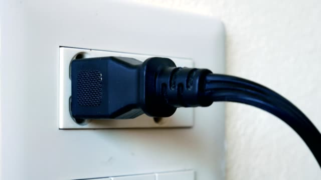man hand plugging in a power cable and then unplugging it in a typical electrical outlet cover - close up view