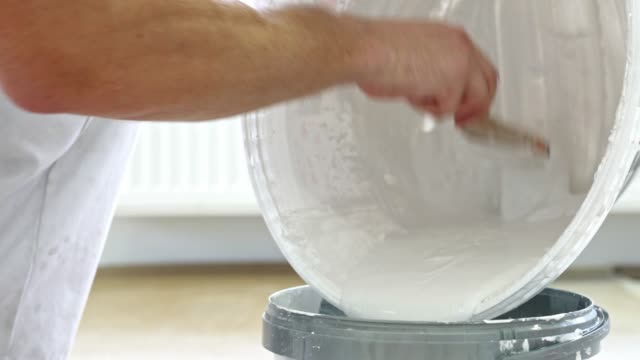 man hand scrapping the excess wall paint out of the bucket with a brush - bucket stock videos & royalty-free footage