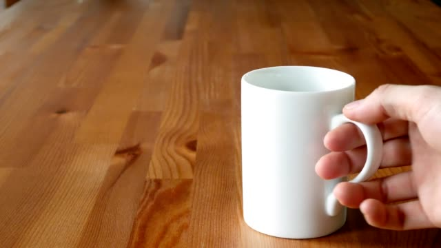man hand stirring coffee in a cup with teaspoon on wooden table - teaspoon stock videos and b-roll footage