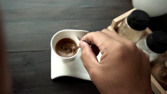 stockvideo's en b-roll-footage met man hand roeren epresso koffie. - foam hand