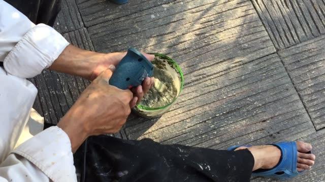 Mann mit der Hand rührt Farbe