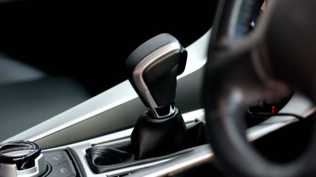 man hand switching gear stick in car. driver. transport - car interior stock videos & royalty-free footage