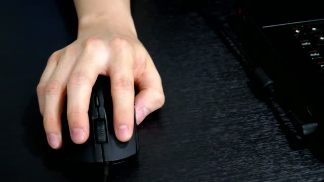 man hand using computer mouse and working with laptop computer on office table - close up view