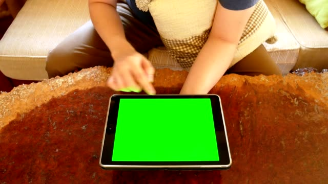 man hand using digital tablet computer with mock up green screen for chroma key in living room - indoor scene