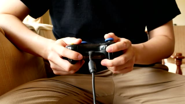 man hand using game controller to play video game in living room - dolly shot - hobby video stock e b–roll