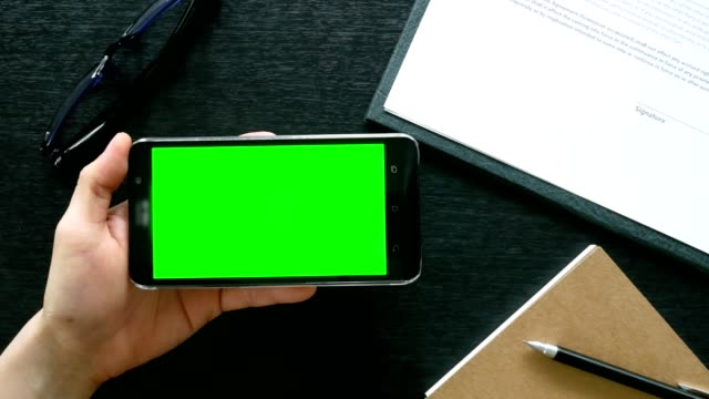 man hand using mobile phone with green screen on office table - top view - timber stock videos and b-roll footage