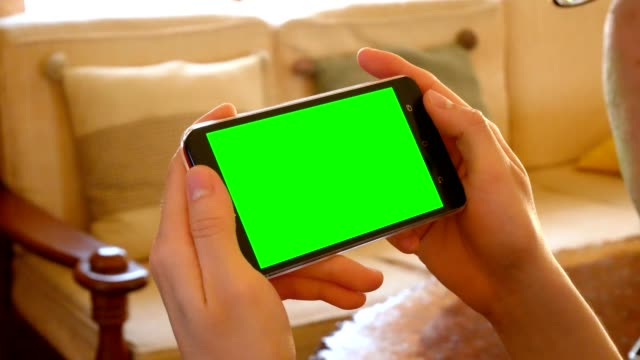 man hand using mobile phone with mock up green screen for chroma key in living room - domestic indoor scene