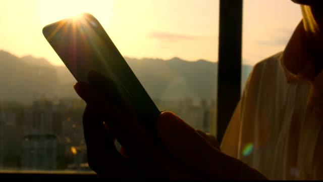 vídeos de stock, filmes e b-roll de mão do homem usando o telefone no por do sol - equipamento