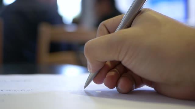 男は紙に手書き、クローズ アップ。 - ペン点の映像素材/bロール