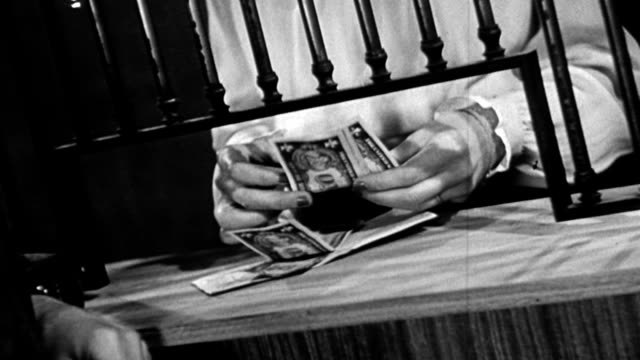 Man handing dollar bills to woman bank teller through window / woman counts dollar bills Close up bank teller counting money on January 01 1945