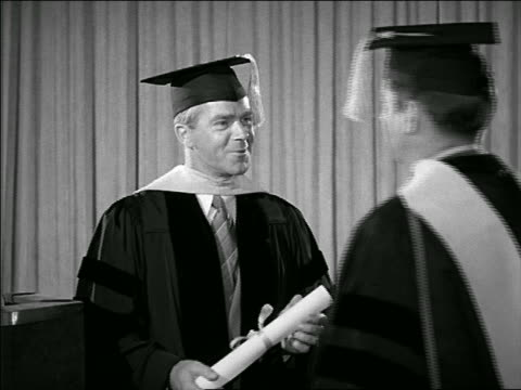 B/W 1952 man handing other man diploma indoors