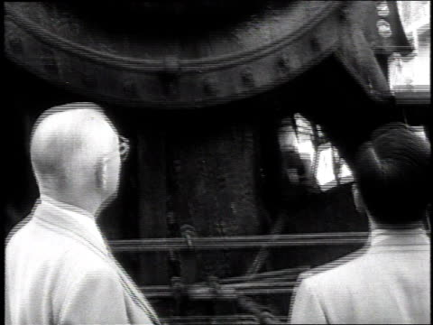 man handing over the contract for locomotives to korea / kids hanging out the side of train / locomotive being hoisted onto a ship - 1954 stock videos & royalty-free footage