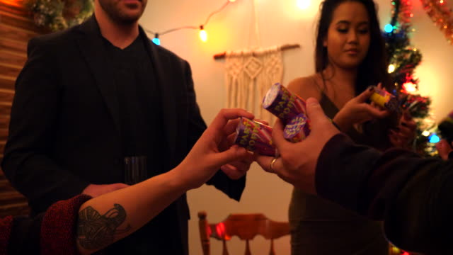 cu man handing party poppers to friends during holiday party in living room - decoration stock videos & royalty-free footage