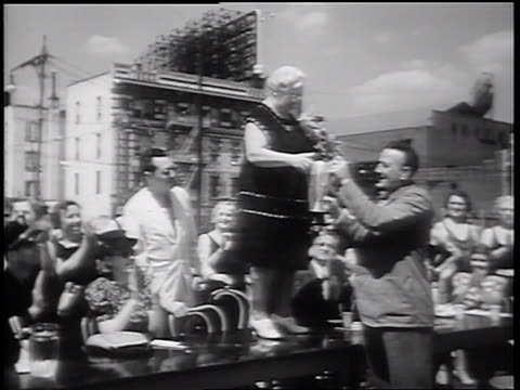 b/w 1939 man handing trophy to senior beauty pageant winner standing on judge's table - spielkandidat stock-videos und b-roll-filmmaterial