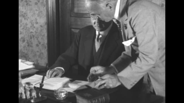 man hands document to pres herbert hoover sitting at desk hoover signs document man reaches over with blotting paper / note exact year not known... - herbert hoover us president stock videos & royalty-free footage