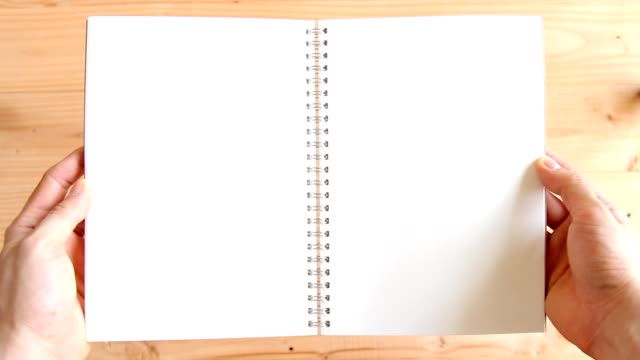 man hands opening empty blank notebook on wooden background - use for template - template stock videos and b-roll footage