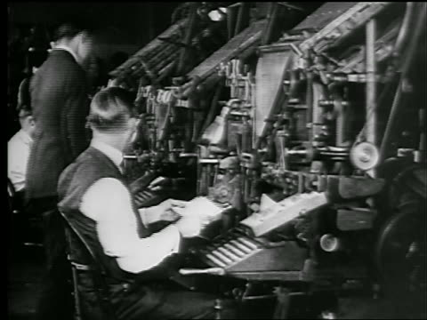 B/W 1927 man hands paper to second man at typesetters in newspaper office / newsreel