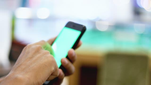 男性スマートフォンを手にタッチしたり、スクロール緑色の画面 - 押す点の映像素材/bロール