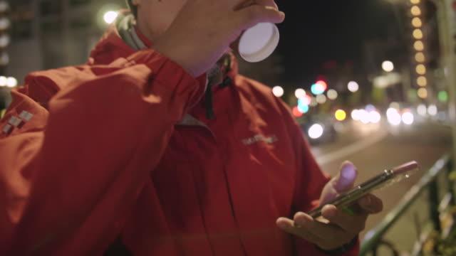 夜にスマートフォンを使って手を使う男。 - オーバーコート点の映像素材/bロール