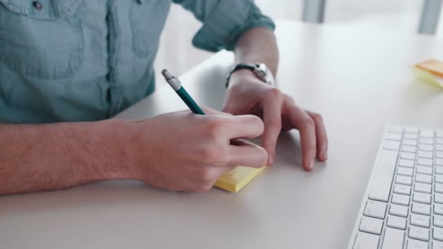 man hands writing on a post it in a office - animal pen stock videos & royalty-free footage