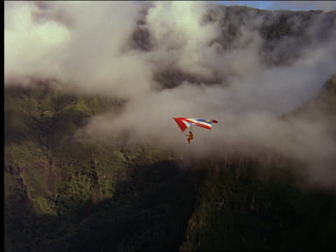 AERIAL man hang gliding over clouds and mountains