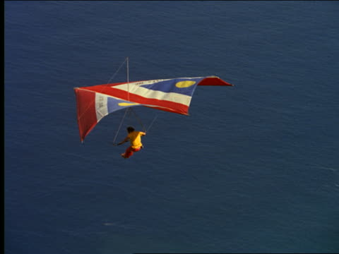 aerial man hang gliding over ocean + mountain - hang gliding stock videos and b-roll footage