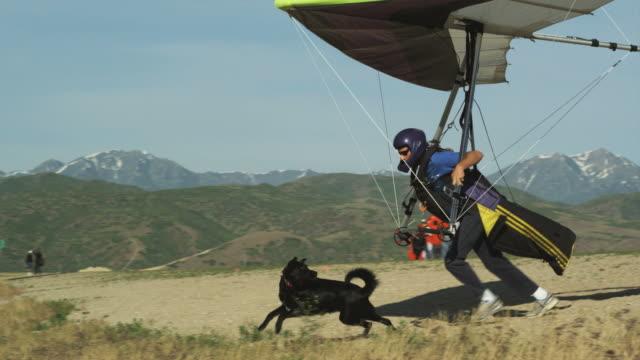 WS PAN POV Man hang gliding while dog follows behind / Lehi, Utah, USA.