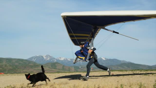 WS PAN POV Man hang gliding while dog running behind / Lehi, Utah, USA.