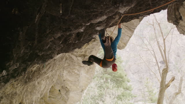 vídeos y material grabado en eventos de stock de man hanging and rock climbing on ceiling of cave opening / american fork canyon, utah, united states - american fork canyon