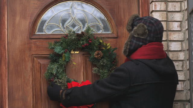 stockvideo's en b-roll-footage met ms man hanging christmas wreath on door  / newark, new jersey, usa - krans