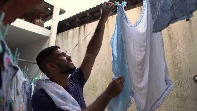 vídeos de stock, filmes e b-roll de homem pendurando roupas no varal - pendurar