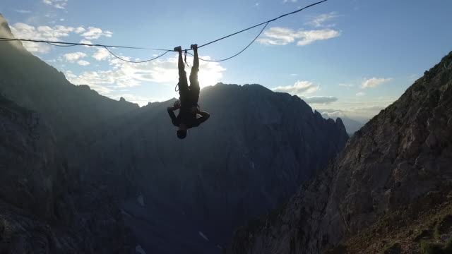 man hanging head down on a highline in the alps - upside down stock videos & royalty-free footage