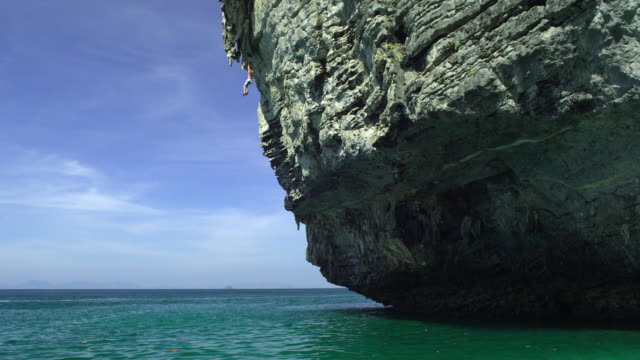 ws man hanging off cliff and jumping into sea, krabi, thailand - see other clips from this shoot 1459 stock videos and b-roll footage