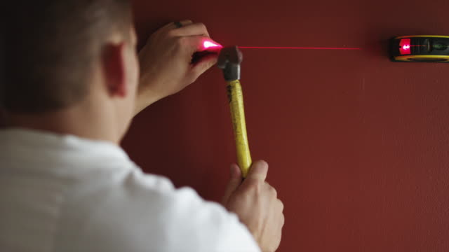 MS Man hanging picture on wall using laser level / Orem, Utah, USA
