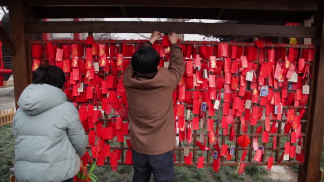 ms man hanging prayer offerings for good luck at temple fair to celebrate chinese spring festival / xi'an, shaanxi, china - luck stock videos & royalty-free footage