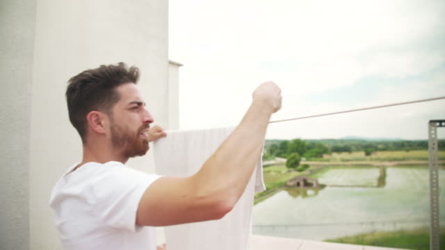 man hanging up clothes after laundry - washing line stock videos & royalty-free footage