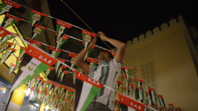 man hangs banner with uae flags - deira, dubia - vereinigte arabische emirate stock-videos und b-roll-filmmaterial