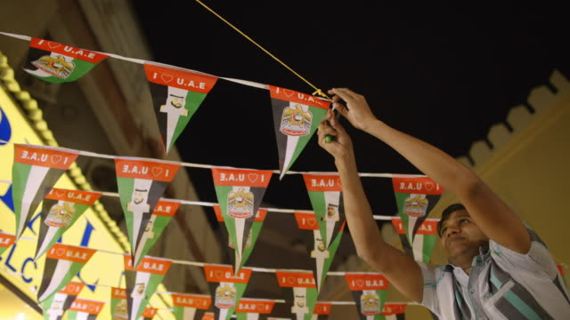man hangs banner with UAE flags - Deira, Dubia
