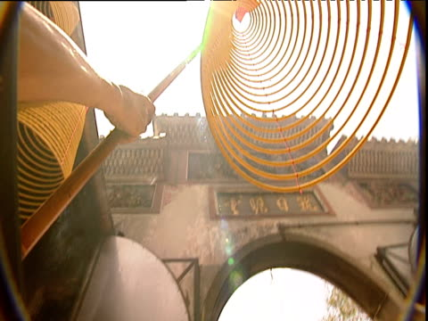 stockvideo's en b-roll-footage met man hangs burning incense coil in temple courtyard hong kong - gelovige