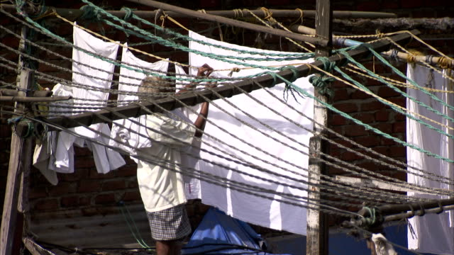 A man hangs laundry out to dry in India.