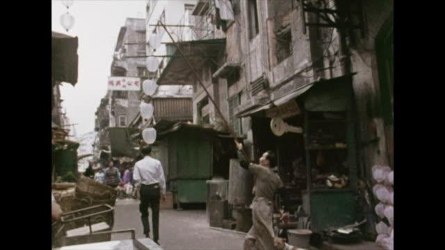 a man hangs paper lanterns outside a shop; hong kong, 1972 - hong kong stock videos & royalty-free footage