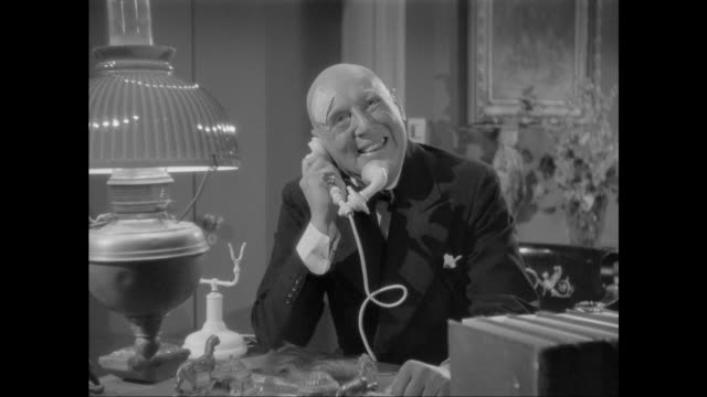 1946 man happily flirts with woman on telephone - solutions stock videos & royalty-free footage
