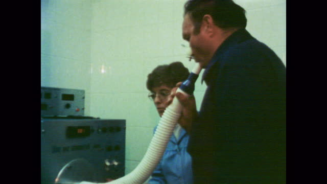 1978 man has chest x-ray before breathing into a tube before coughing - 胴体点の映像素材/bロール