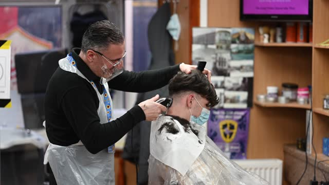 man has his hair cut at lazarou hair salon and barbers on churchill way on march 15, 2021 in cardiff, wales. hairdressers in wales could reopen for... - cutting hair stock videos & royalty-free footage